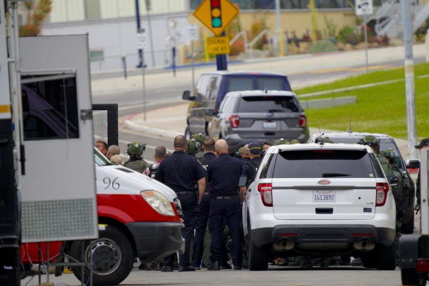 Police officers gather during SWAT standoff