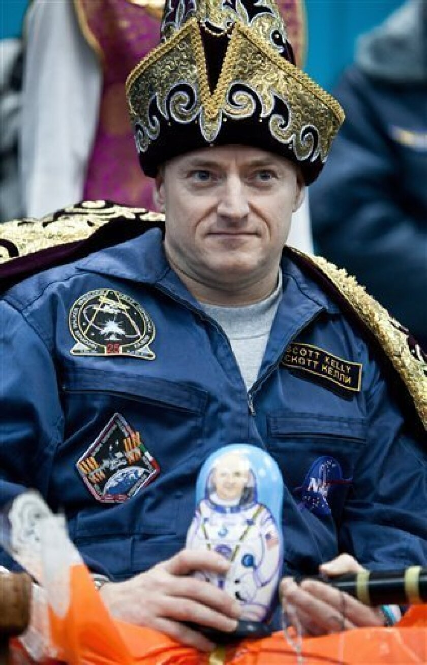 US astronaut Scott Kelly dressed in Kazakh folk outfit holds a Russian traditional matroyshka doll during a news conference in Kustanai, after landing near the town of Arkalyk, northern Kazakhstan, Wednesday, March 16, 2011. NASA astronaut Scott Kelly and two Russian cosmonauts landed safely Wednesday in the snowy expanses of central Kazakhstan after spending a five-month stint on the International Space Station. (AP Photo/Dmitry Kostyukov, Pool)