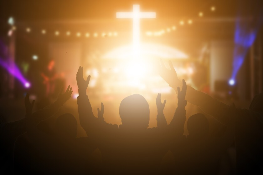 Christians raising their hands in praise and worship at a night music concert.