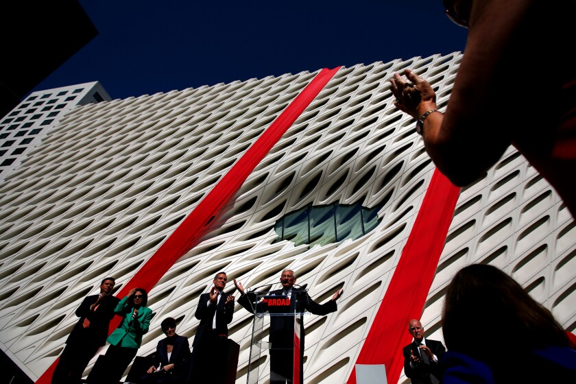 Eli Broad stands with arms outstretched at a lectern in front of a white contemporary art museum with two large red ribbons