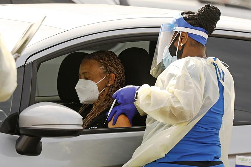 A healthcare worker gives a vaccine through an open car window.