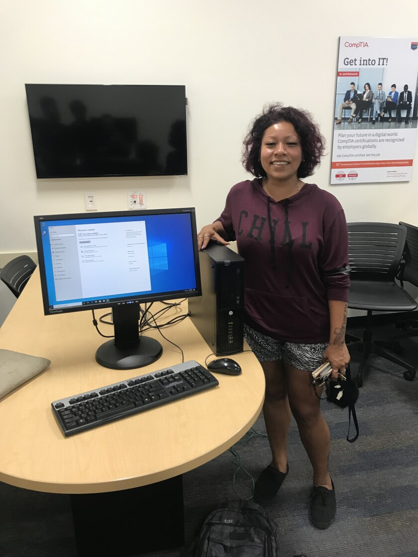 MiraCosta College student Fabi Redding with one of the refurbished computers.