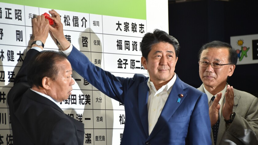 Japanese Prime Minister and ruling Liberal Democratic Party President Shinzo Abe, center, places a rosette on an LDP candidate's name to indicate an election victory in Tokyo on July 10, 2016.