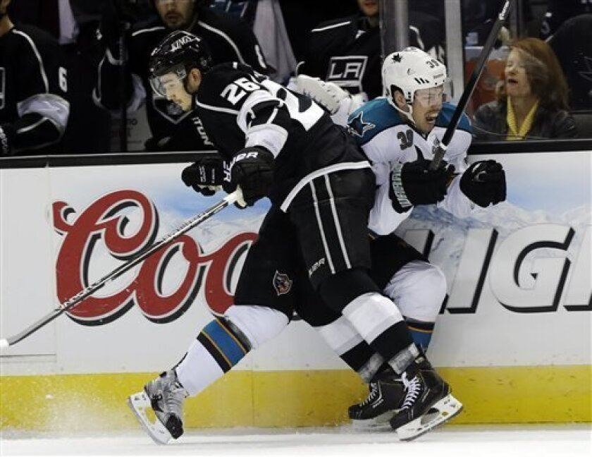 San Jose Sharks center Logan Couture (39) collides with Los Angeles Kings defenseman Slava Voynov, of Russia, during the first period of an NHL hockey game in San Jose, Calif., Tuesday, April 16, 2013. (AP Photo/Marcio Jose Sanchez)