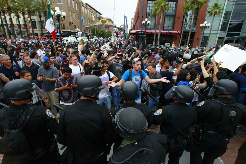 Protestors plead with San Diego police officers in riot gear, hoping to remain in the Gaslamp Quarter where they had been throughout the rally for Donald Trump Friday at the San Diego Convention Center.