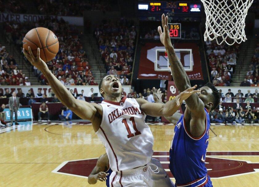 Oklahoma guard Isaiah Cousins (11) shoots as Kansas forward Jamari Traylor, right, defends in the first half of an NCAA college basketball game in Norman, Okla., Saturday, Feb. 13, 2016. (AP Photo/Sue Ogrocki)