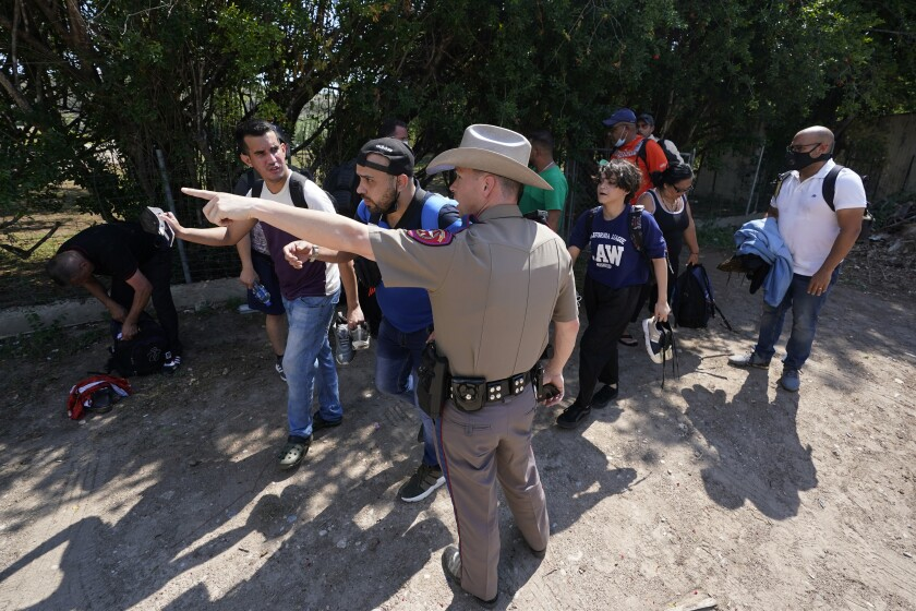 ARCHIVO - En esta fotografía de archivo del miércoles 16 de junio de 2021, un agente del Departamento de Seguridad Pública en Del Rio, Texas, dirige hacia un lugar a un grupo de migrantes que cruzaron la frontera y se entregaron a las autoridades. (AP Foto/Eric Gay, Archivo)