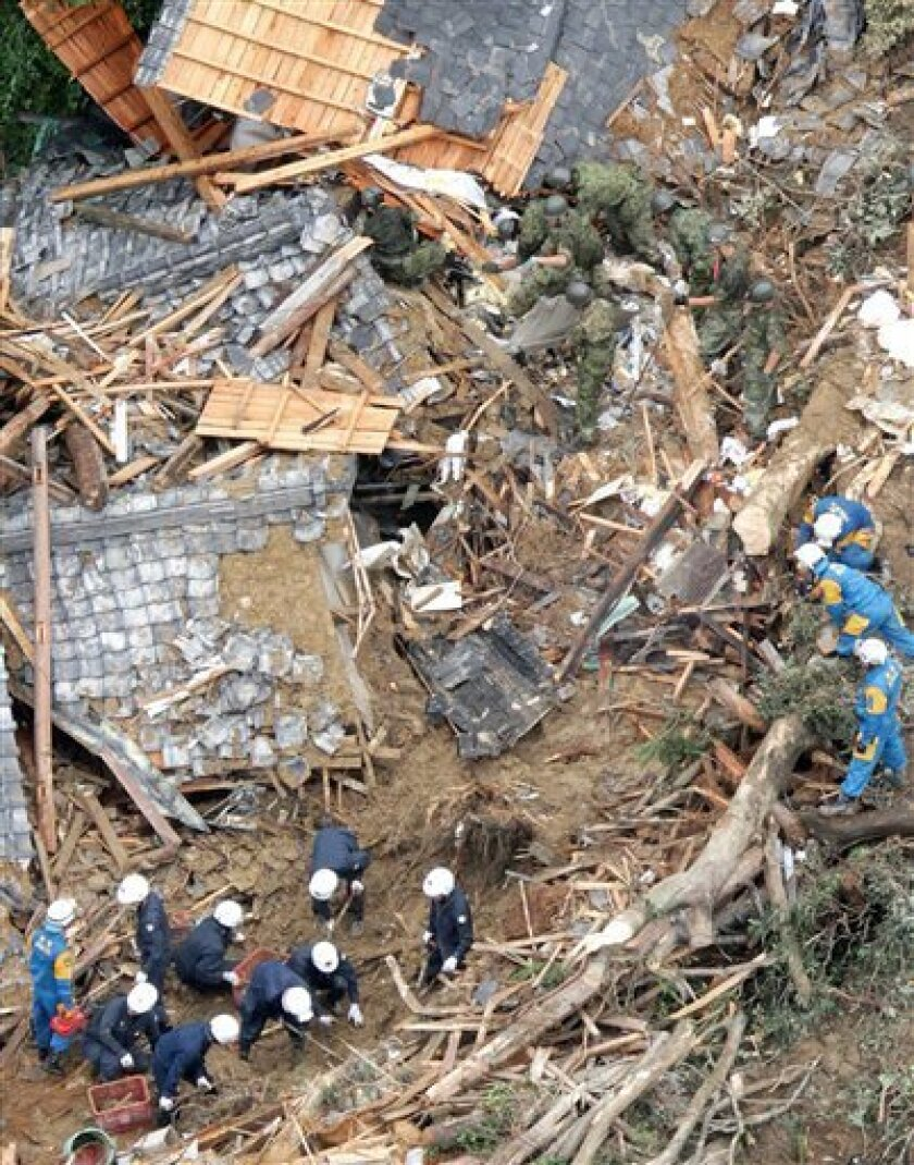 Japanese soldiers and police officers search destroyed houses for missing people after a landslide triggered by Typhoon Talas that brought heavy rains at Tanabe, central Japan, Monday, Sept. 5, 2011. The storm dumped record amounts of rain Sunday in western and central Japan as it turned towns into lakes, washed away cars and triggered mudslides that obliterated houses. (AP Photo/Kyodo News) JAPAN OUT, MANDATORY CREDIT, NO LICENSING IN CHINA, FRANCE, HONG KONG, JAPAN AND SOUTH KOREA