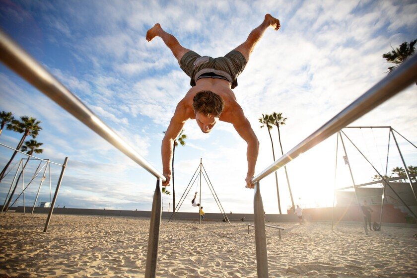 Brian Comstock, 29, does a hand stand on exercise bars at Muscle Beach on Friday.