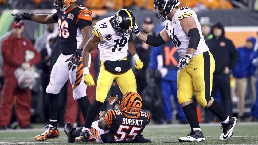 Pittsburgh's JuJu Smith-Schuster stands over Cincinnati 's Vontaze Burfict after injuring the Bengals player with a helmet hit during the teams' game on Dec. 4.