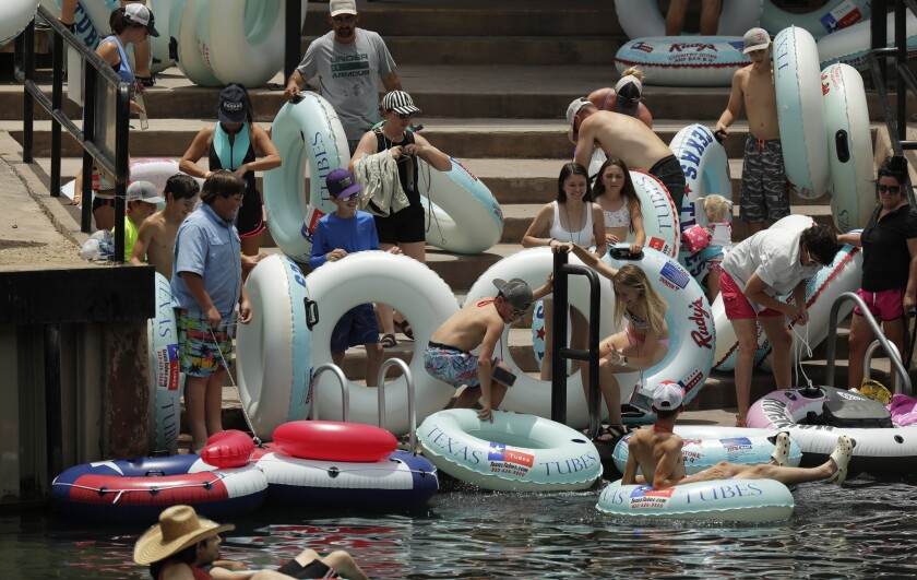 People prepare to inner-tube along the Comal River on Thursday in New Braunfels, Texas.