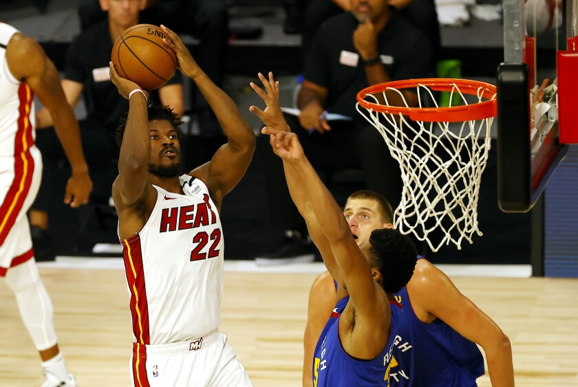 The Heat's Jimmy Butler shoots over Nuggets defenders Saturday in Florida.