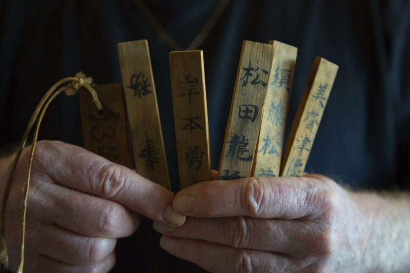 Jim Armstrong of Pacific Beach holds seven items his father took from a dead Japanese pilot in Hawaii. They are believed to be prayer sticks and a military identification tag.