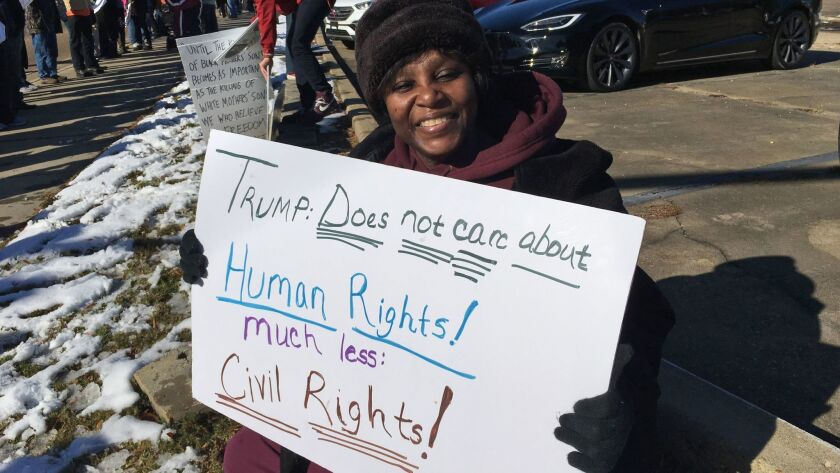 Gladys Bunzy, of Jackson, Miss., protests Saturday, Dec. 9, 2017, against the visit of President Don