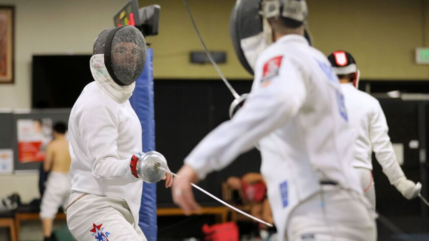 Bailey (left) has a fencing bout with Marc Kuritz during an evening practice session at the San Diego Fencing Center.