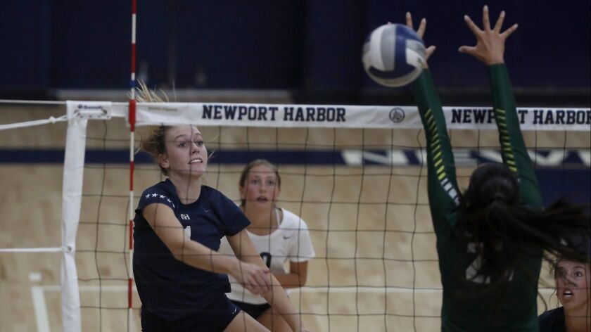 Newport Harbor High's Kendall Bagby, left, spikes the ball against Edison during the second set in a