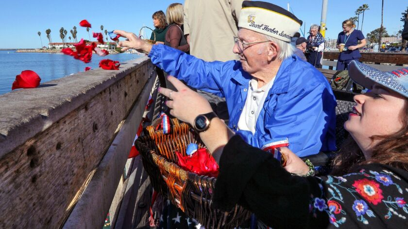At the Pearl Harbor Memorial event at Oceanside Harbor in December, 98-year-old Pearl Harbor survivor John Quier and his great-granddaughter Melissa Sterling, 24, toss rose petals in the water in memory of those killed in the attack. Quier passed away on Feb. 15.