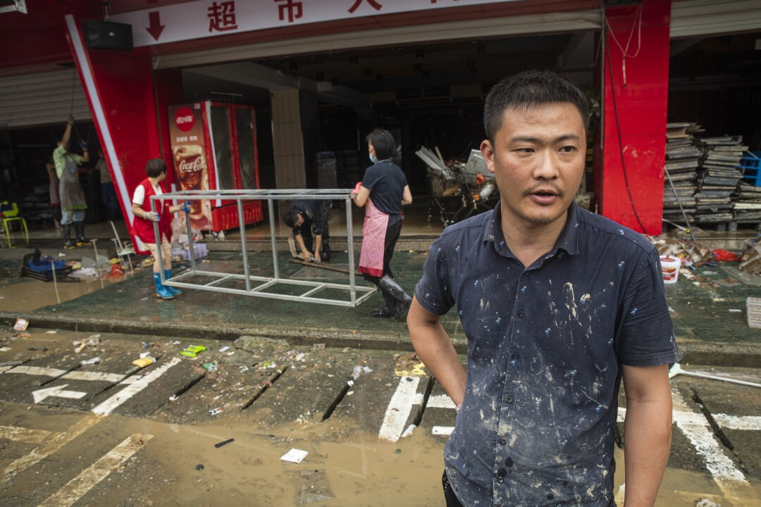 Yin Jianfeng, manager of a flooded supermarket in Shexian, Anhui province, stands outside as employees clean up