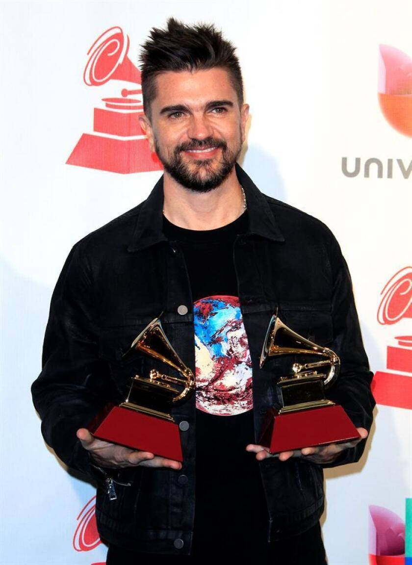 """El cantante colombiano Juanes sostiene sus premios a """"Mejor álbum pop/rock"""" y """"Mejor ingeniería para álbum"""" durante los XVIII Premios Grammy Latinos. EFE/Archivo"""