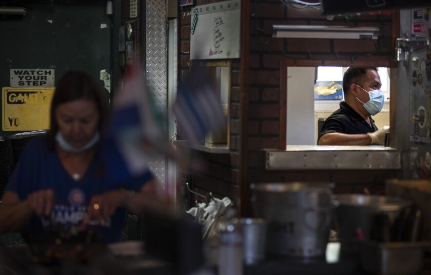 Bartender Julie Radtke and chef Miguel Barrow  prepare takeout orders at Kelly's Korner Tavern.