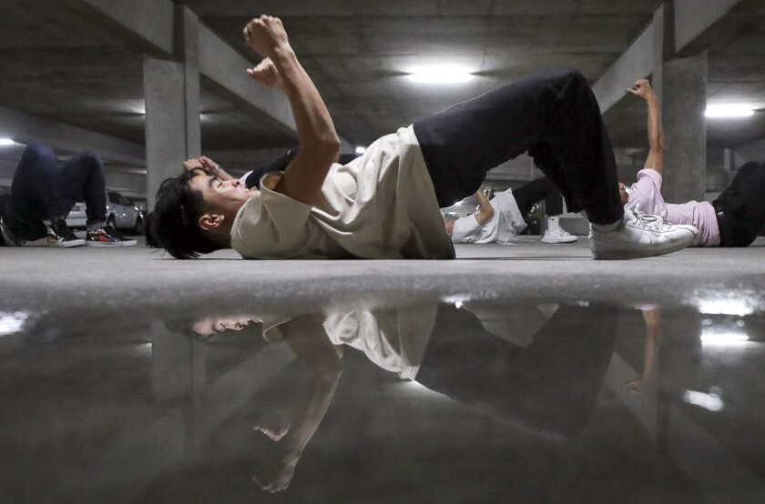 Joshua Candelria, 19, is reflected in a water puddle as he and other members of a hip-hop dance group perform during the end of the year choreography project put on by the SDSU Vietnamese Student Organization Modern, a collegiate hip-hop dance troupe, in a parking garage on the SDSU campus on Thursday, December 5, 2019 in San Diego, California.