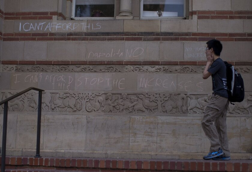 A student walks past a chalk-written protest against tuition hikes on the wall outside Powell Library at UCLA on Tuesday.