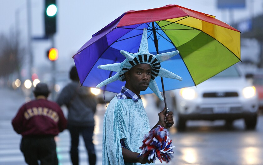Wayne Elzy, 37, dressed up as the Statue of Liberty, keeps dry while trying to draw people's attention to a nearby tax office in South Los Angeles.