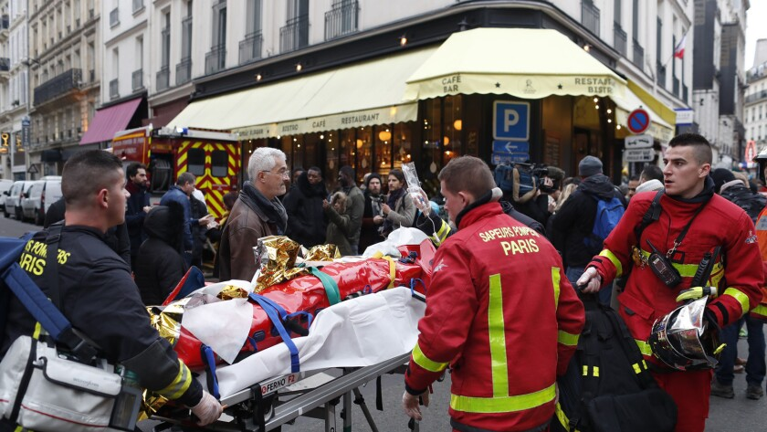 Firefighters evacuate a wounded man on a stretcher from the scene of a gas leak explosion in Paris,