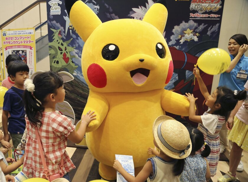 """In this Monday, July 18, 2016 photo, a stuffed toy of Pikachu, a Pokemon character, is surrounded by children during a Pokemon festival in Tokyo. """"Pokemon Go,"""" a compulsive smartphone game has not been made available to the Japanese public yet as of Wednesday, July 20, 2016, as a rumor circulated on the internet that it would come out on that day. (AP Photo/Koji Sasahara)"""