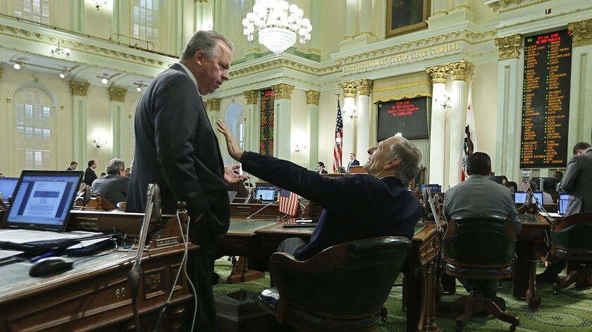 State Sen. Bill Dodd (D-Napa), left, discusses his disaster insurance bill with Assemblyman Bill Quirk (D-Hayward) on Thursday in Sacramento.
