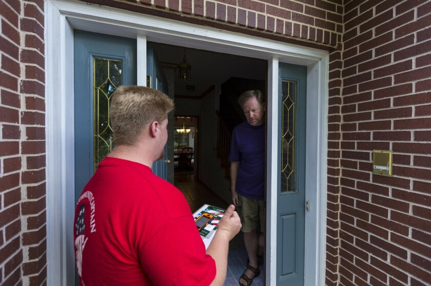 In this photo taken June 29, 2016, Wisconsin Republican party door-to-door canvasser Andy Andrews, left, talks with homeowner Jim Fulton in Fitchburg, Wis. An Associated Press review of Republican Party operations in important presidential election states finds there are fewer employees than the na