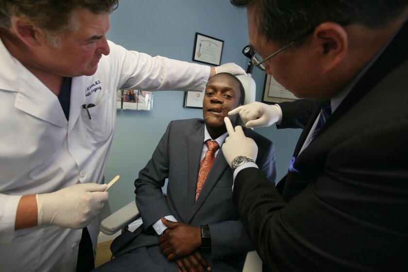 Dr. Thomas Vecchione, left, and Dr. James Chao performed a check-up on Blessing Makwera this month in San Diego.