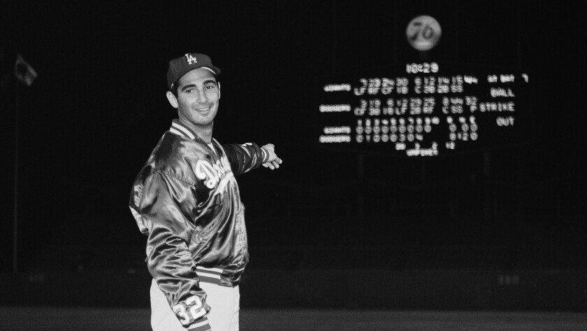 Sandy Koufax points at the Dodger Stadium scoreboard after throwing a perfect game against the Chicago Cubs on Sept. 9, 1965.