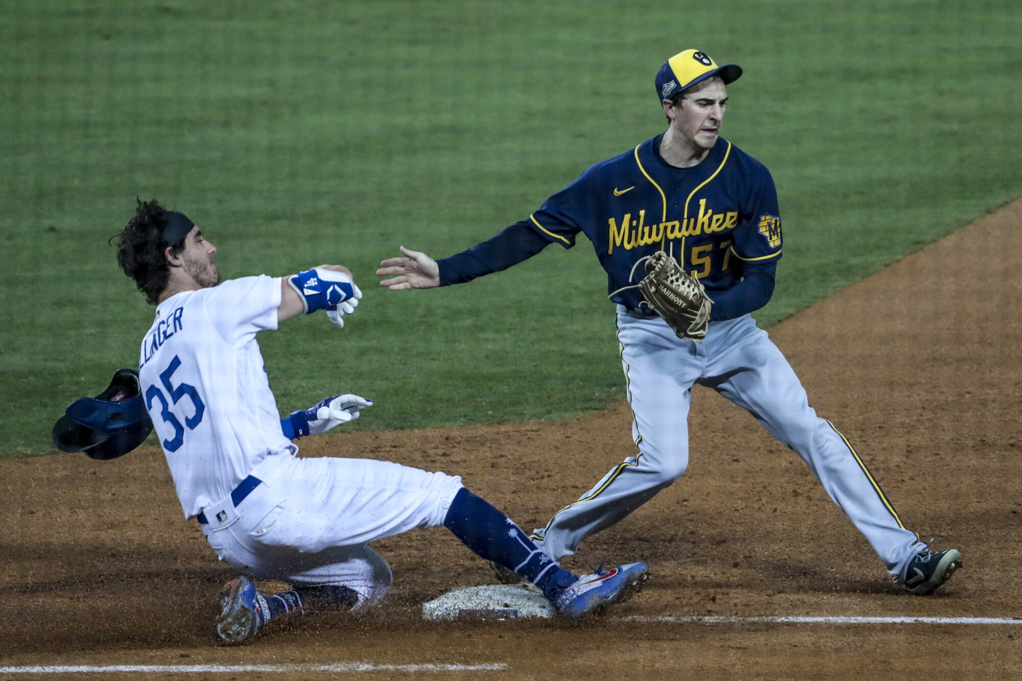 Milwaukee Brewers relief pitcher Eric Yardley, right, beats Dodgers center fielder Cody Bellinger to first base.