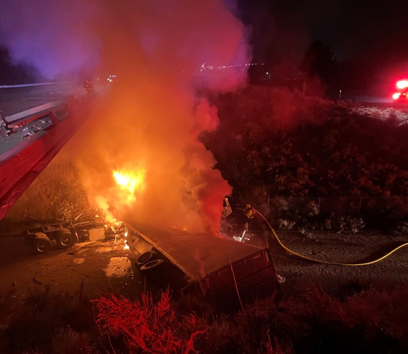 Firefighters work to extinguish flaming big rig Wednesday night after it crashed off I-8 bridge in the East County mountains.