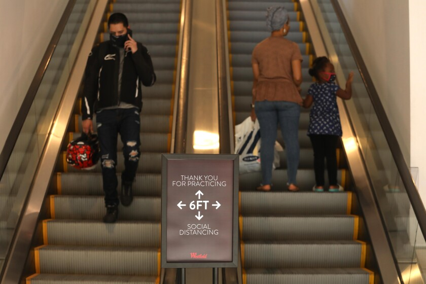 A sign in front of an escalator reminds shoppers to keep six feet apart
