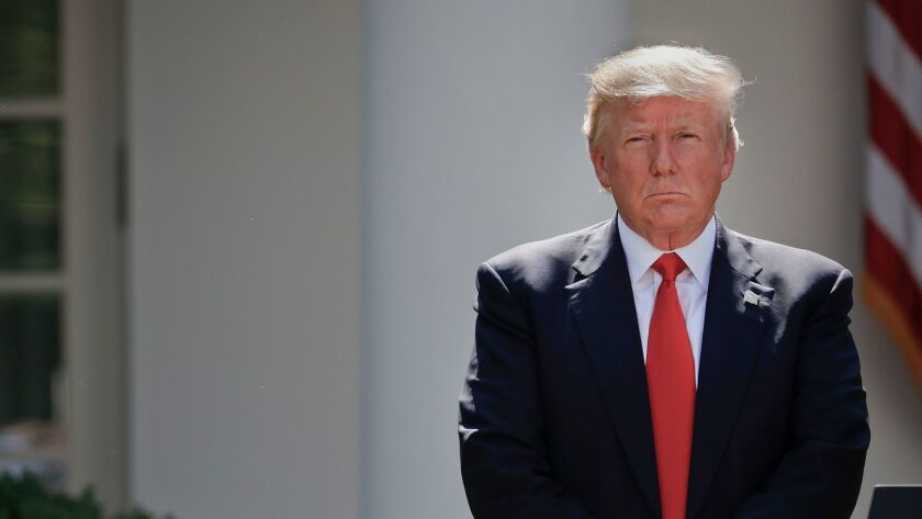 President Trump stands next to the podium after speaking about the U.S. role in the Paris climate change accord, Thursday in the Rose Garden of the White House.