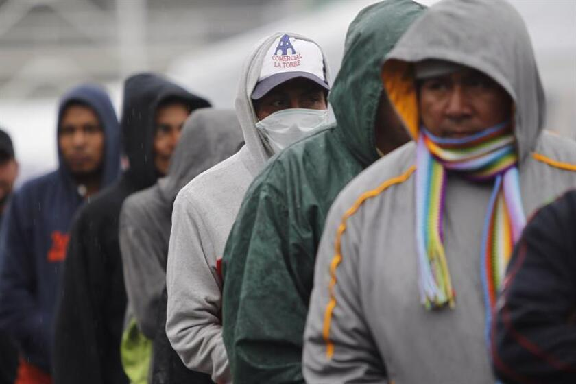 A group of Central American migrants protect themselves from the cold as they stand in line at the Jesus Martinez 'Palillo' sports stadium in Mexico City, Mexico, Nov. 14, 2018. EPA-EFE/Sashenka Gutierrez