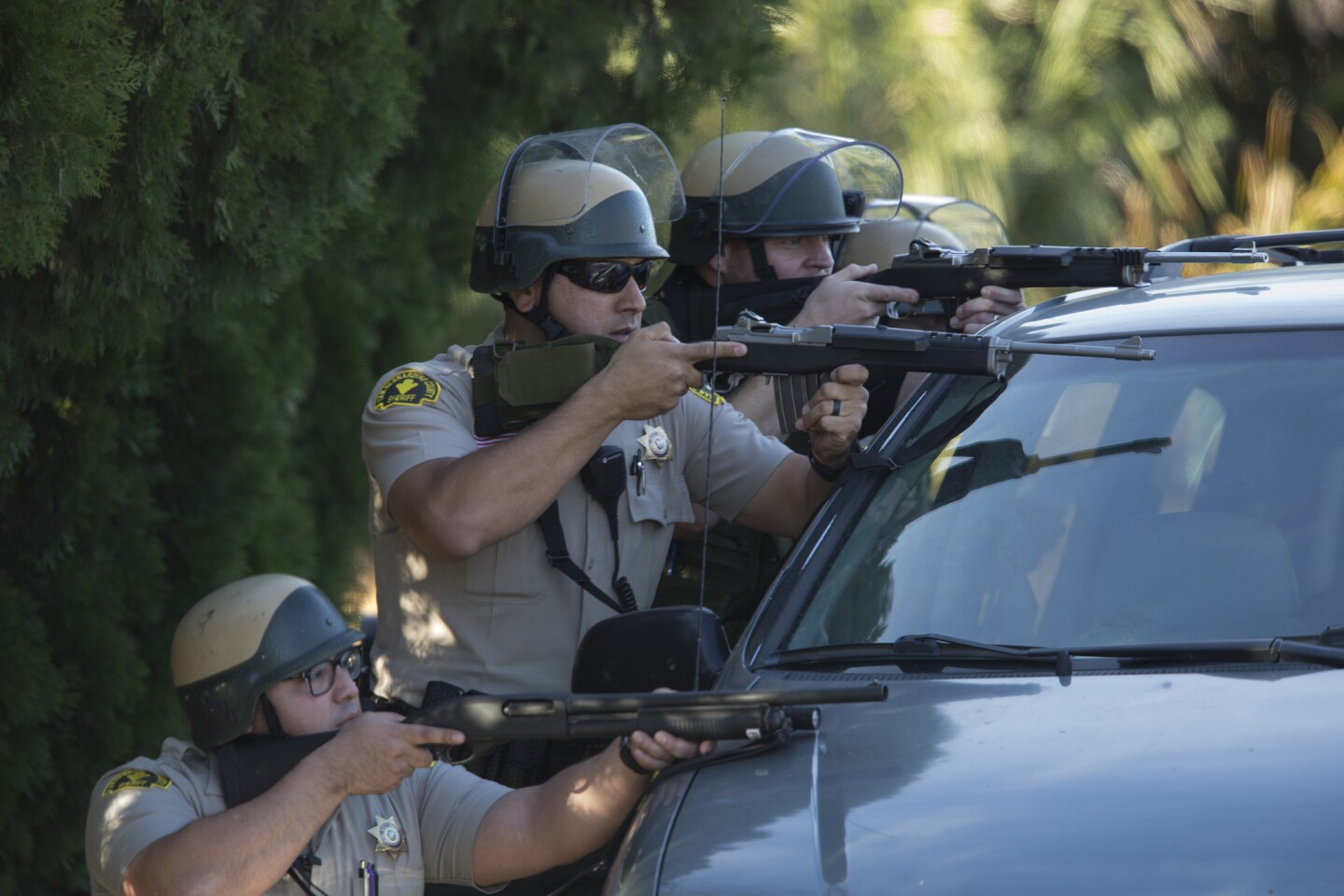San Bernardino County sheriff's deputies draw guns behind a minivan on Richardson St. during a search for suspects involved in the mass shooting of 14 people at the Inland Regional Center in San Bernardino.