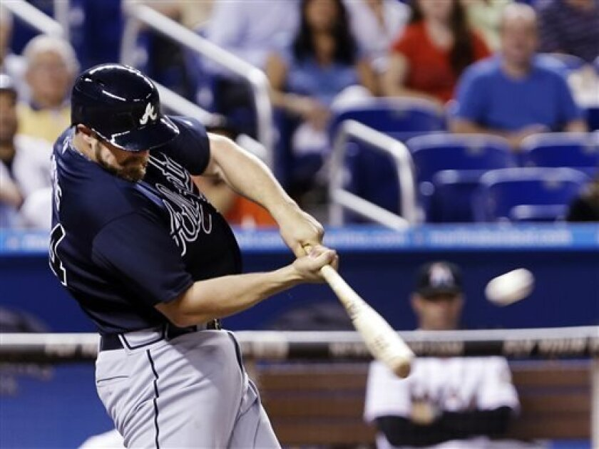 Atlanta Braves' Evan Gattis hits a three-run home run during the fifth inning of a baseball game against the Miami Marlins, Wednesday, April 10, 2013, in Miami. Andrelton Simmons and Jason Heyward scored on the hit. (AP Photo/Wilfredo Lee)
