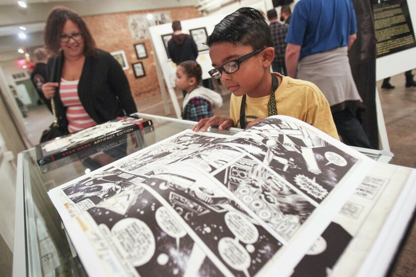 """Nine-year-old Darin Soto looks through a book of Star Wars comic art at the """"The Art of Star Wars"""" exhibit."""