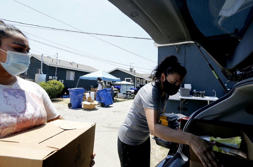 Gabriella Barrera helps load boxes of groceries for Buddy Southeast LA, a  group that helps families ill with COVID-19.