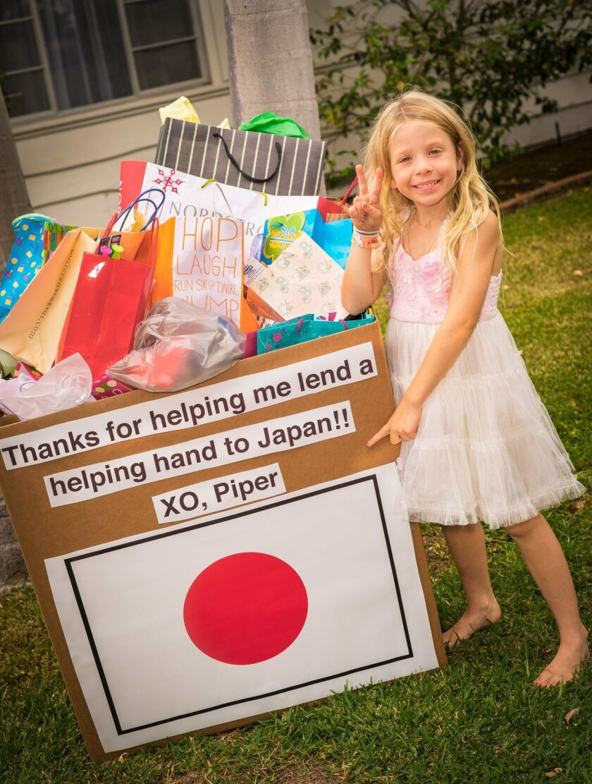 Piper Groff, 7, of La Jolla poses with the clothes and supplies she asked for as gifts for her birthday, which will be sent to children affected by the 2011 tsunami in Japan.