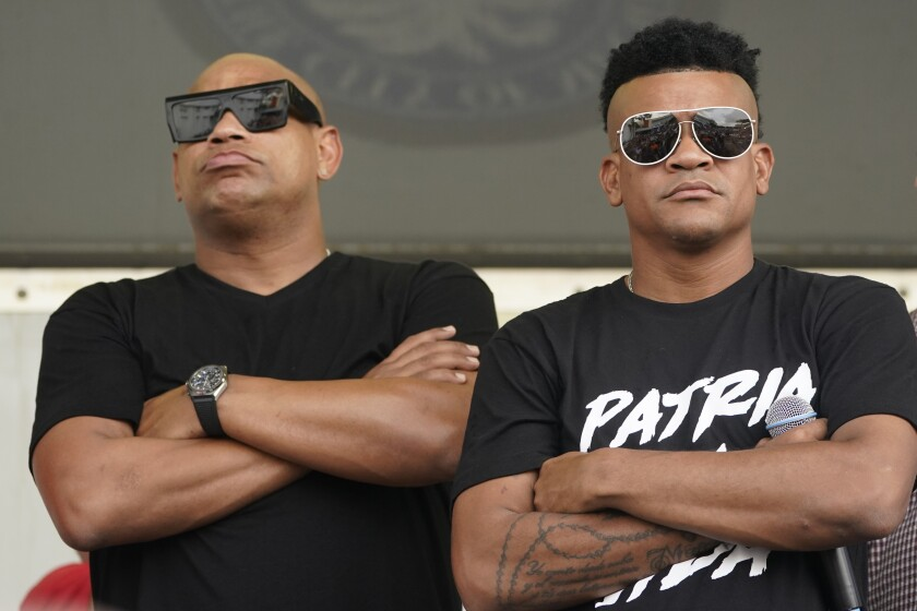 """Cuban reggaeton musicians Alexander Delgado, left, and Randy Malcom, both with the band Gente de Zona, look out into a crowd of demonstrators, Wednesday, July 14, 2021, in Miami's Little Havana neighborhood, as people rallied in support of antigovernment demonstrations in Cuba. Gente de Zona's song """"Patria y Vida,"""" which means Homeland and Life, has become the anthem of the demonstrations and is a play on the phrase """"Patria o Muerte,"""" Homeland or death, which was a phrase in the Cuban Revolution. (AP Photo/Wilfredo Lee)"""