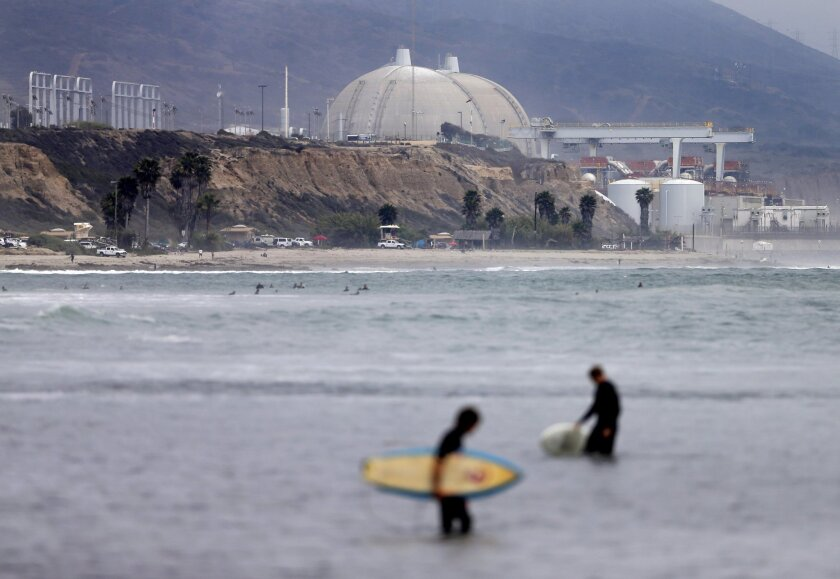 Surfers pass in front of the San Onofre nuclear power plant, owned by Southern California Edison