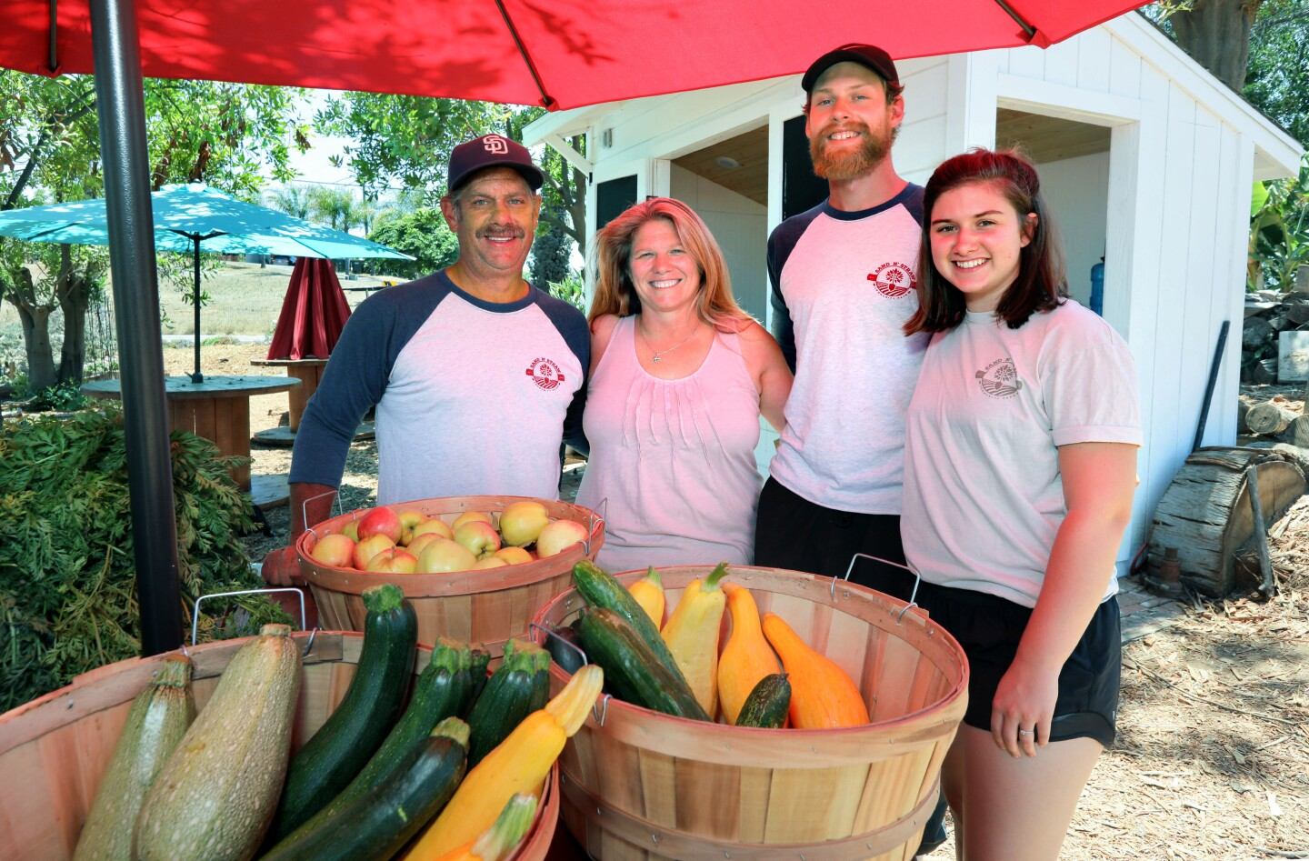 Family farmers Rich and April Viles, left, with their son Jonathan Viles and his wife, Jenna, at Sand n' Straw community Farm in Vista.