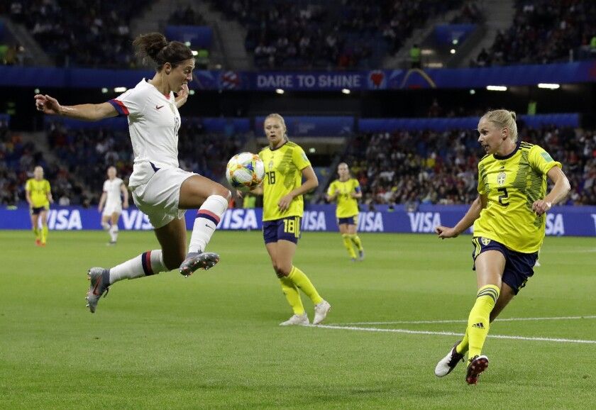 United States' Carli Lloyd, left, leaps as she attempts to control the ball as Sweden's Jonna Anders