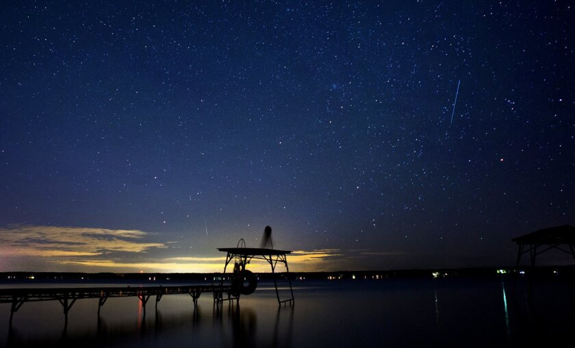 A meteor from the Perseid meteor shower streaks across the night sky in this view from the west side of Seneca Lake in Penn Yan, N.Y.
