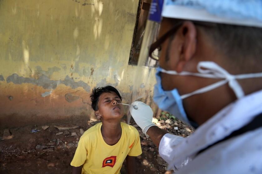 Un trabajador sanitario toma una muestra nasal a un niño para una prueba de detección del coronavirus,