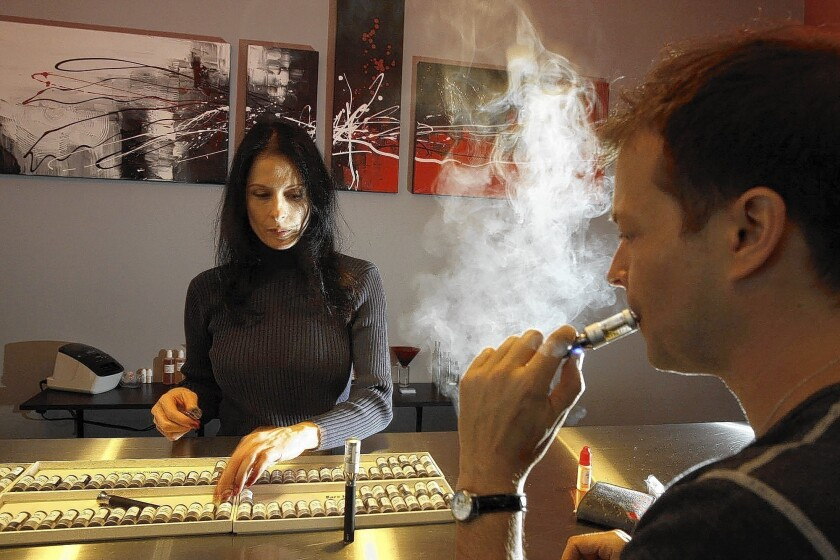 Jason Wingo, 42, vapes at Natural Vapes in Los Angeles as Elaine Ruggieri looks on. Wingo smoked for 10 years and says vaping helped him quit. Los Angeles City Council voted Tuesday to impose the same restrictions on e-cigarettes as on traditional tobacco products.